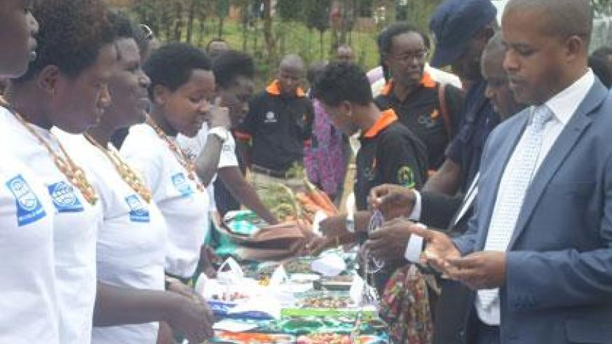The Director General of WDA, Jerome Gasana, with other officials visit the art and craft stand at the exhibition during the certificate awarding ceremony. (Grace Mugoya)