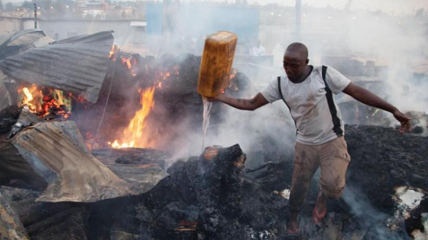 A resident of Gikondo tries to extinguish fire that burnt down businesses in the area recently. Victims of such fires can take long to be paid if they were insured by firms that under price premiums. (File)