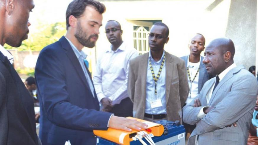 Mobisol's Maier (left) explains how the solar unit works as MTN boss Asante (right) and other officials look on. The firm celebrated its 1,000th installation on Wednesday. (Michel Nkurunziza)