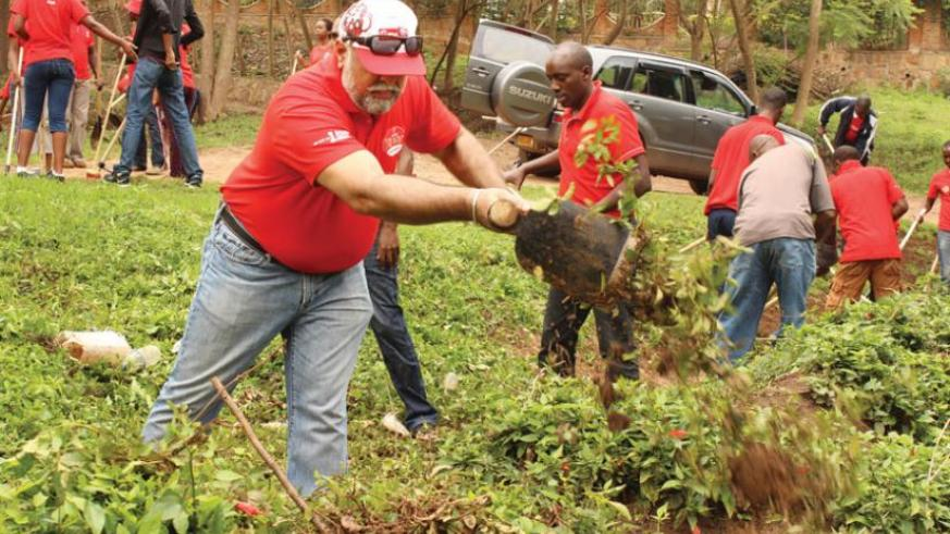 Bhullar (foreground) and other Airtel workers join Kagara village residents during last month's Umuganda. (Courtesy)