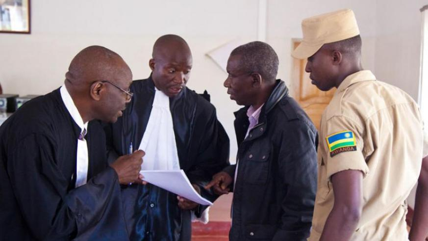 Charles Bandora (R) talks to his lawyers Boniface Nizeyimana (centre) and Ferdinand Mbera after the court session last year. (Timothy Kisambira)
