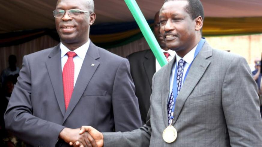 Murekezi (L) congratulates Bank of Kigali chief executive officer James Gatera, upon the bank's being named taxpayer of the year. (Courtesy)