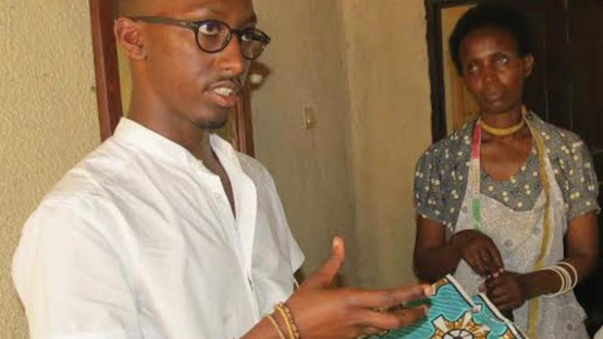 Matthew Rugamba, House of Tayo, a fashion company, proprietor, explains how to make African attire as a seamstress looks on. (File)
