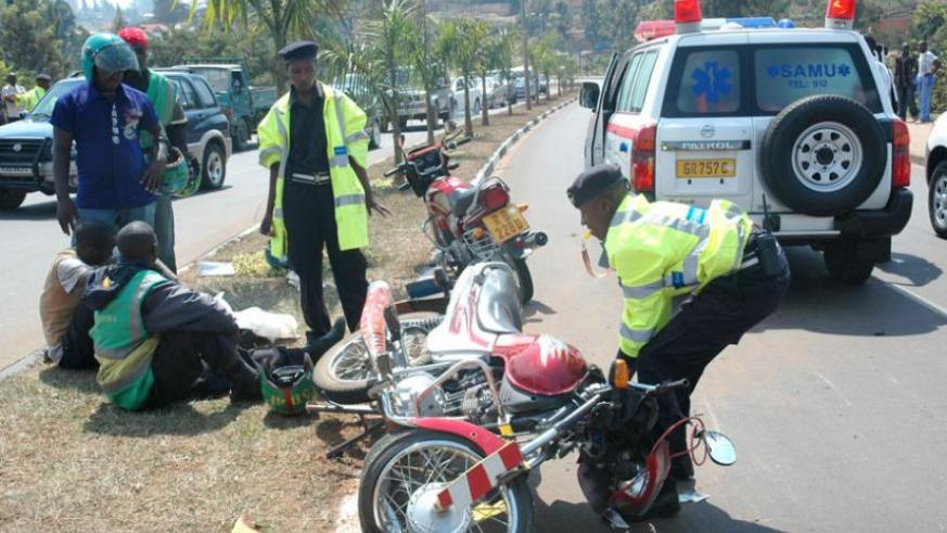 A Police officer removes a motorcycle from the scene of an accident in Kimicanga. (John Mbanda)