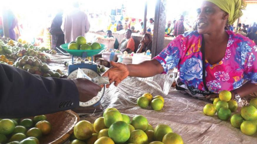 A vendor serves a buyer. Orange prices have doubled to Rwf1,000 year-on-year. (Stephen Rwembeho)