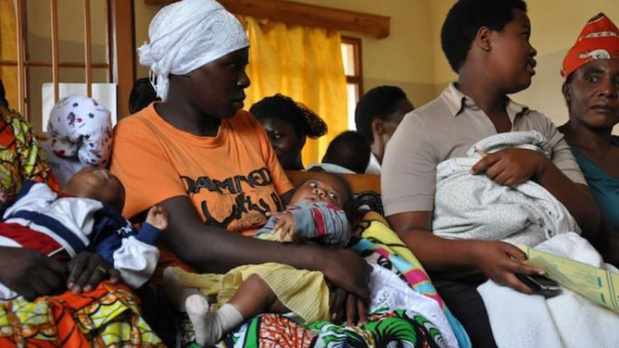 Mothers carry their children at a health centre. (Net Photo)