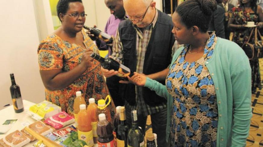Christine Murebwayire (left) shows packaged banana wine to clients in a 2014 picture. SMEs like hers must make planning an essential component of their businesses. (File)