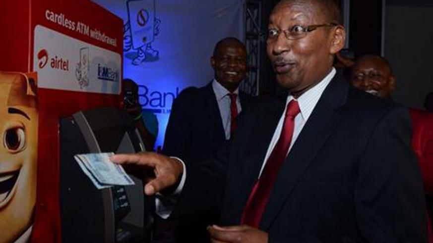 Central bank chief John Rwangombwa withdraws at an I&M Bank ATM using Airtel Money. The card-less withdrawal is facilitated by RSwitch's e-payment services (File)