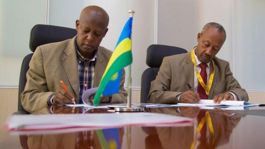 Silas Udahemuka the RCAA director general (left) and Gobena Guangul, the deputy director general of Ethiopia's Civil Aviation Authority, sign agreement documents last week. (Timothy Kisambira)