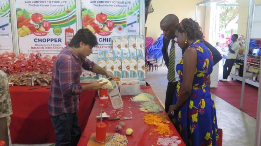An exhibitor demonstrates how modern kitchenware works at the expo. (Francis Byaruhanga)