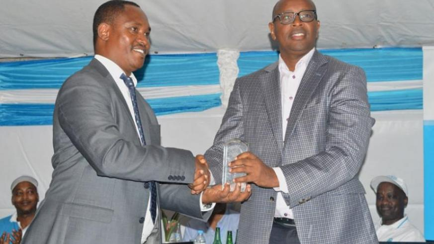 Sano (L) presents the Global Water Leaders' Award to Musoni during May Day celebration on Sunday. (Emmanuel Ntirenganya)