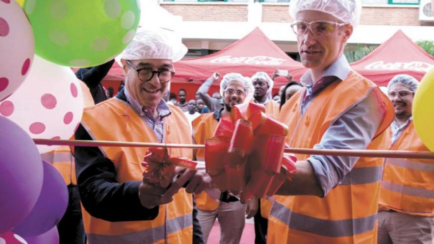 Jonathan Hall (L), the Vice Chairman of the Board and Managing Director of Bralirwa cuts the ribbon during the launch of PET line in Kigali yesterday.  (Teddy Kamanzi)