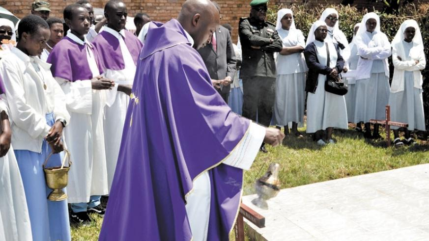 Fr Jean Claude Ndatimana of the Carmelite Fathers sprinkles incense on the monument erected at Save Parish in remembrance of the nuns killed in the Genocide. (E. Ntirenganya)