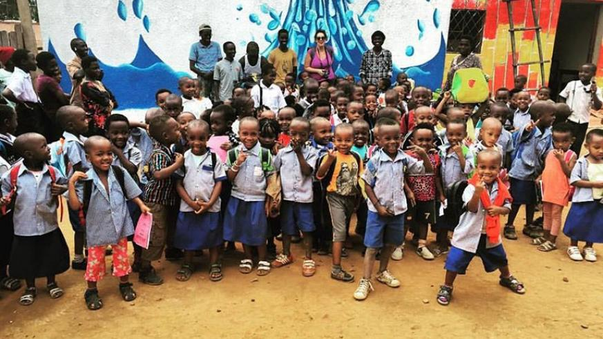School pupils and the artists pose for a photo in front of one of the painted walls. (Moses Opobo)