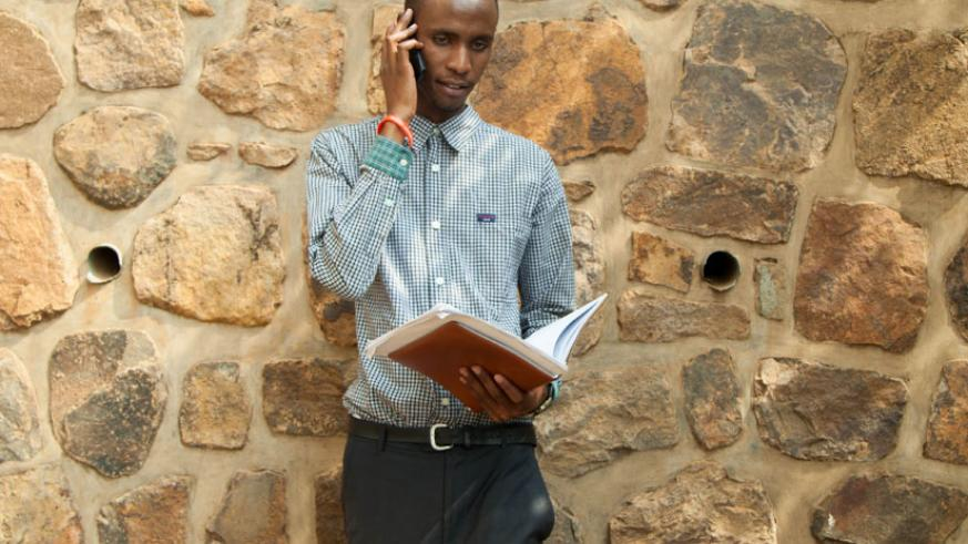 A student talks on phone. Research studies suggest that over-use of a cell phone can be disruptive to the learning process. / Francis Byaruhanga