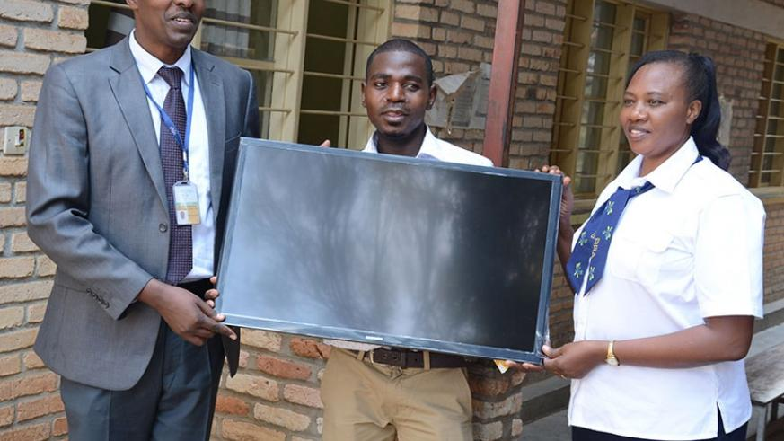 Ntarwerero receives a TV screen from Mbera (left) and Mary Mukarwego, the principal revenue officer at RRA Muhanga District branch, at the event. / Appolonia Uwanziga.