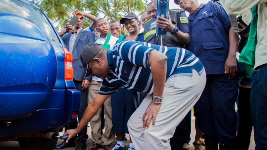 The Minister for Natural Resources, Dr Vincent Biruta, tests levels of carbon emissions from a car as police officers verify if the results match with the environmental standards. / File