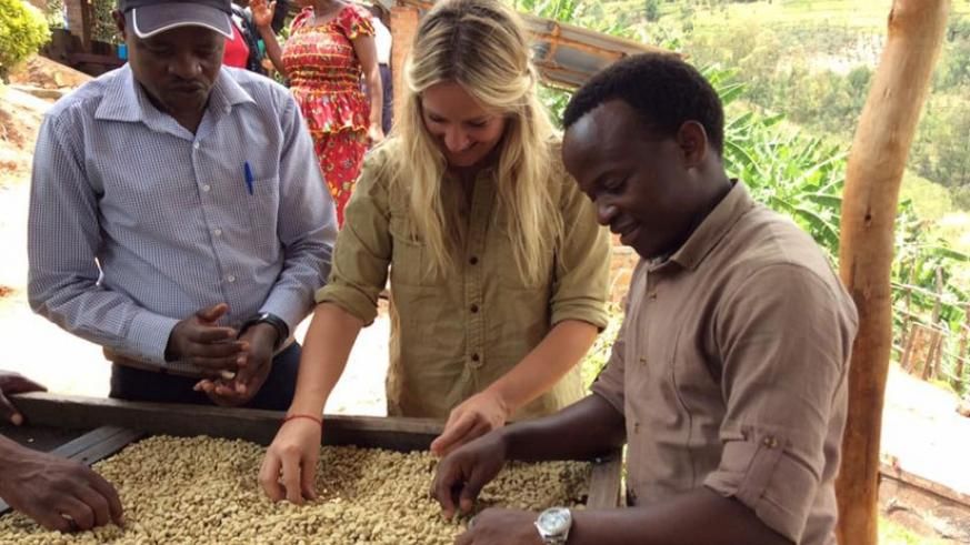 Murindababisha (right) is joined by his customers to spread coffee beans on drying rack at his factory in Kayonza. (Francis Byaruhanga.)