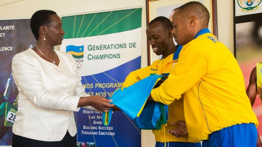 Minister Julienne Uwacu hands over the national flag to the Paralympic team captain Muvunyi (C) and head of delegation, Eric Karasira. (Faustin. Niyigena.)