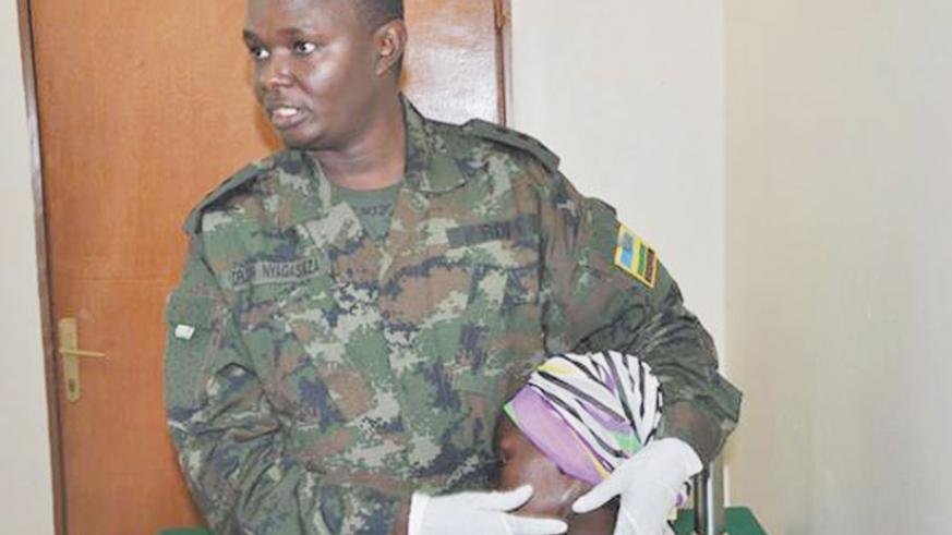 A medic from Rwanda Military Hospital attending to a patient with goiter. / File photo.