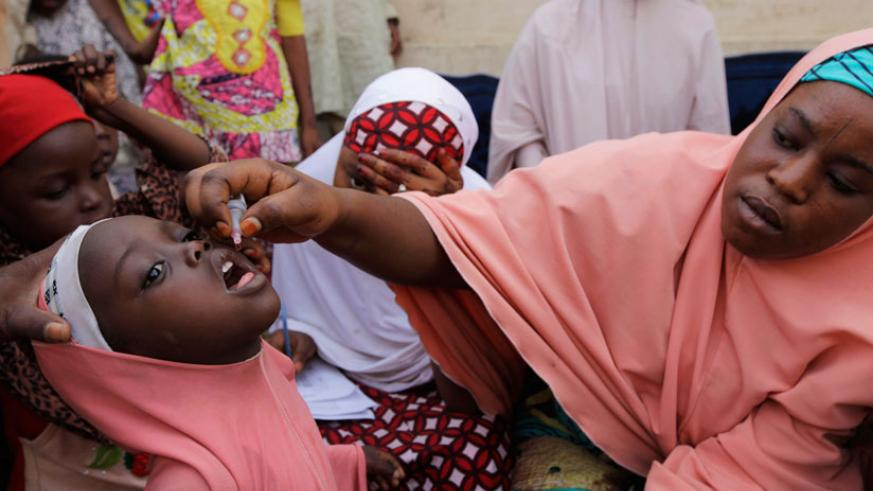 A Nigerian health official administers a polio vaccine to a child in Kano, northern Nigeria. / Internet photo.