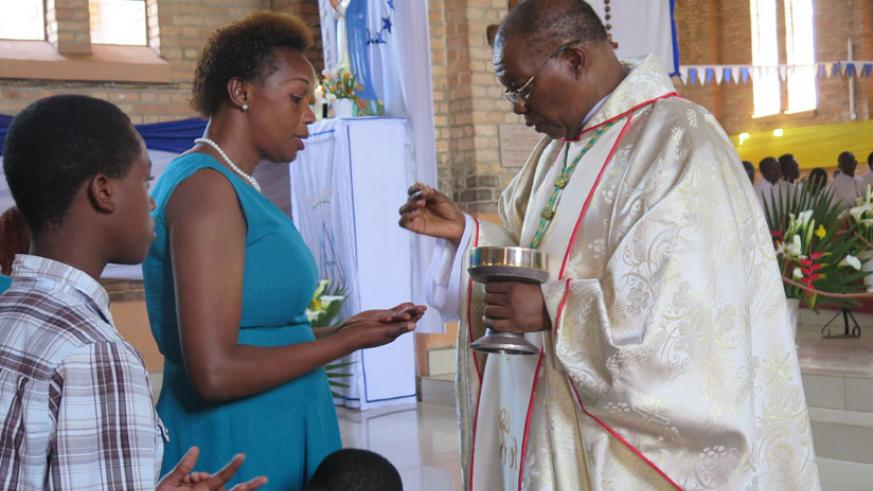 Monsingor Philip Rukamba, the Bishop of Butare Diocese, giving the consecrated bread, Eucharist to Christians during the Chistmas mass at Butare Cathedral last year. / Emmanuel Ntirenganya