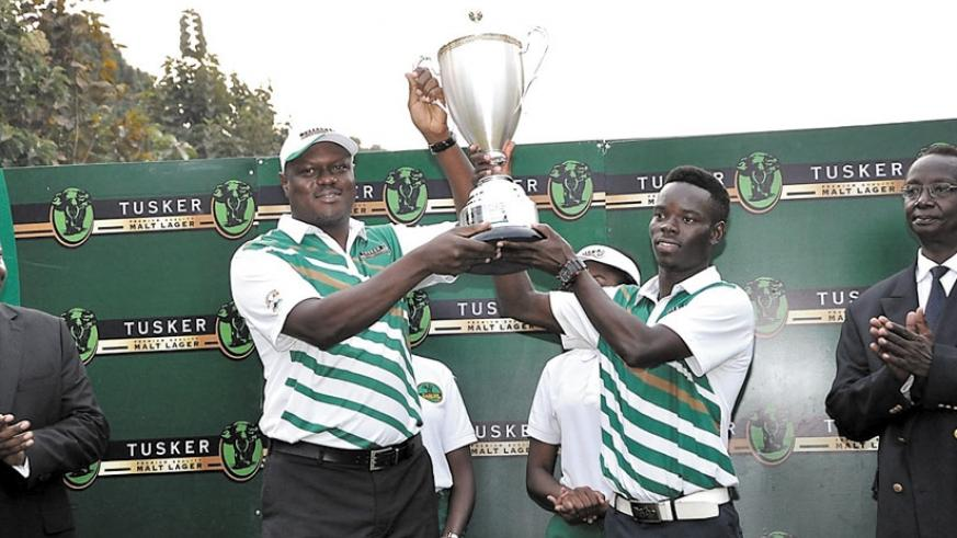 Uganda Breweries Managing Director Mark Ocitti presents the Tusker Malt Uganda Open trophy to Ronald Otile. (Courtesy)