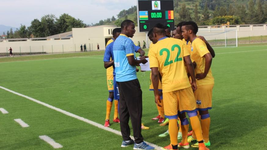 Jimmy Mulisa (left) issues instructions to Amavubi players during a friendly match against Cameroon early this year. / File.