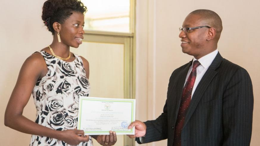 Minister Ndimubanzi (R) certifies one of the new doctors deployed to hospitals yesterday. / Faustin Niyigena.