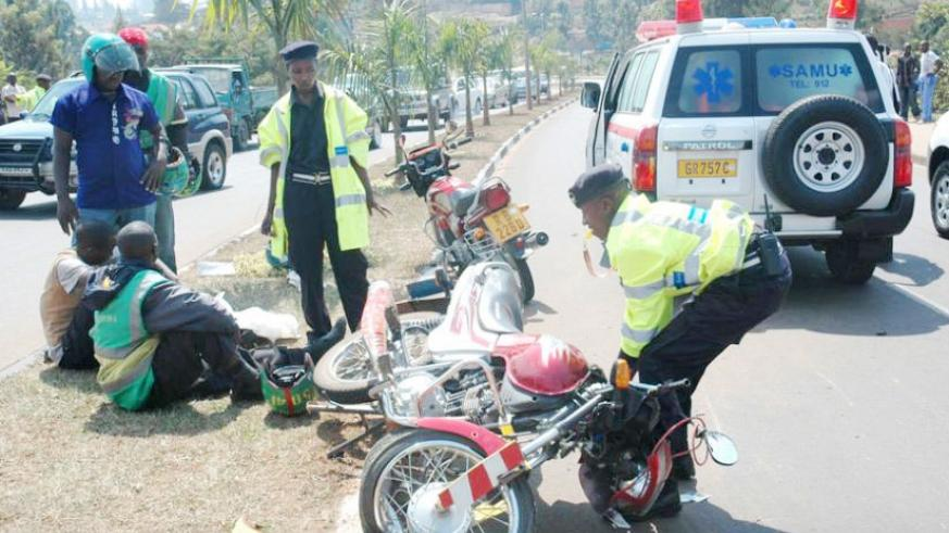 A Police officer removes a motorcycle from the scene of an accident in Kimicanga.