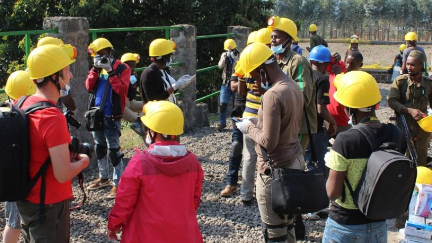 Journalists wear protective gear before entering Musanze caves. / Allan Brian Ssenyonga