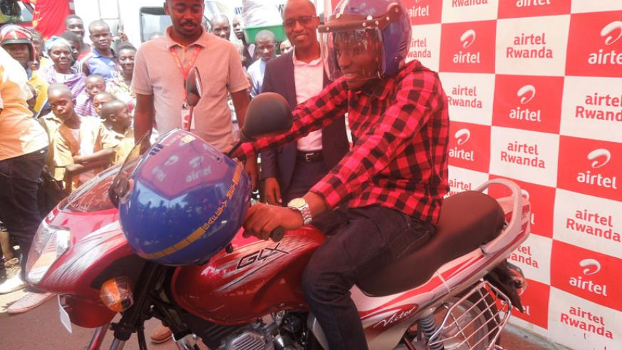 Viateur Irambona tries out the motorbike he won in the promotion. / Appolonia Uwanziga