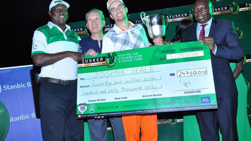 Joshua Seale is handed his winner's cheque by the UBL MD Mark Ociti (L) and the president of the Uganda Golf Union Johnson Omolo (R). (Courtesy)