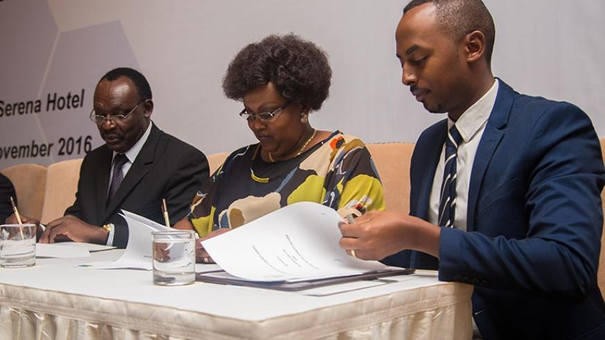 Trade, Industry and East African Community Affairs minister Francois Kanimba (L) signs a memorandum of understanding with the Managing Director of PharmaLab Ltd, Cecile Nkomeje (C), and Serge Kamuhinda, chief operating officer of Rwanda Development Board, in Kigali yesterday. / Faustin Niyigena