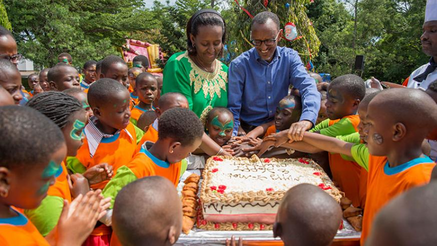 President Kagame and First Lady Jeannette Kagame help children cut End of Year Children's party cake on Sunday at Village Urugwiro. / Courtesy