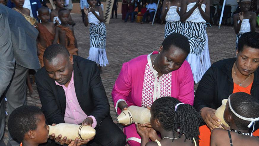 State Minister for primary and secondary education Isaac Munyakazi, Minister Julienne Uwacu and Southern Province governor Marie-Rose Mureshyankwano serve milk to children. / John Mbaraga