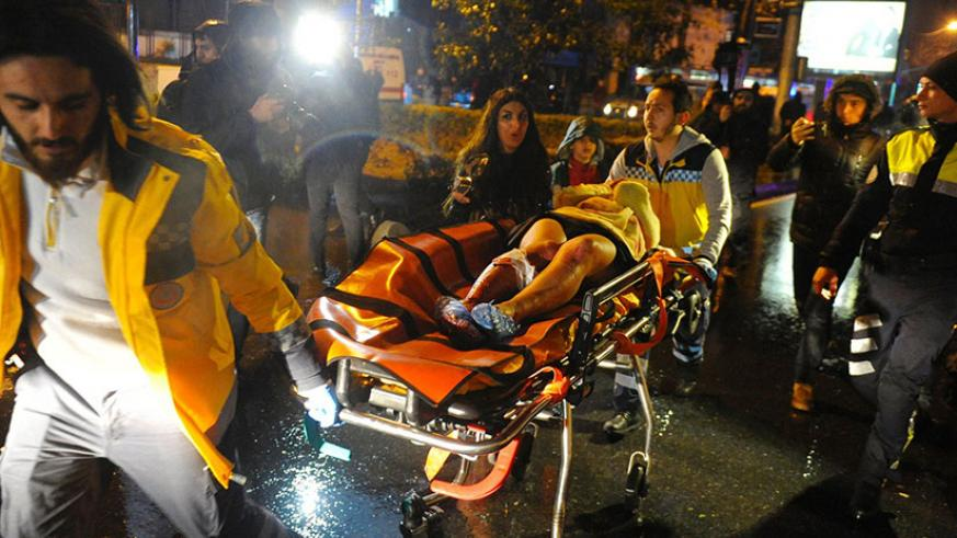 Paramedics carry an injured woman from the site of a mass shooting at an Istanbul nightclub. / Photograph: Ihlas News Agency/AFP/Getty Images