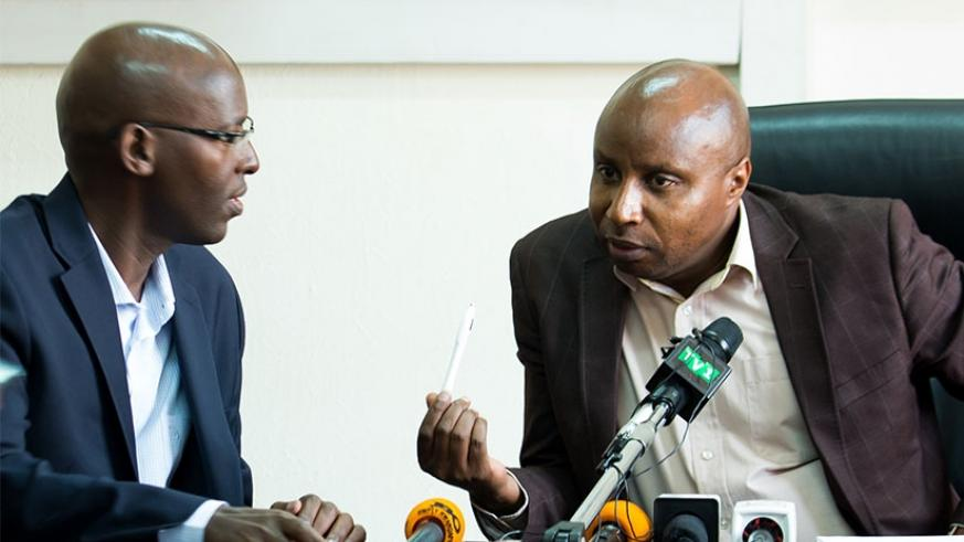 Mugiraneza (R), the Rwanda Energy Group chief executive chats with Eng. Jean Claude Kalisa, the managing director of Energy Utility Corporation Ltd, during the news conference yest....