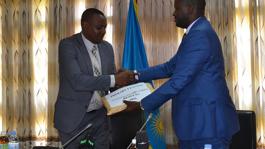 Isaac Munyakazi, the minister of state for primary and secondary education receives PLE results from Janvier Gasana of Rwanda Education Board this morning in Kacyiru. (Jean d'Amour....