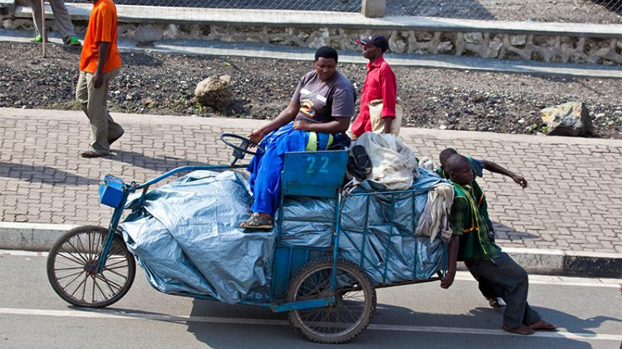 A businesswoman sits on a cart transporting goods from DR Congo to Rubavu. / Timothy Kisambira