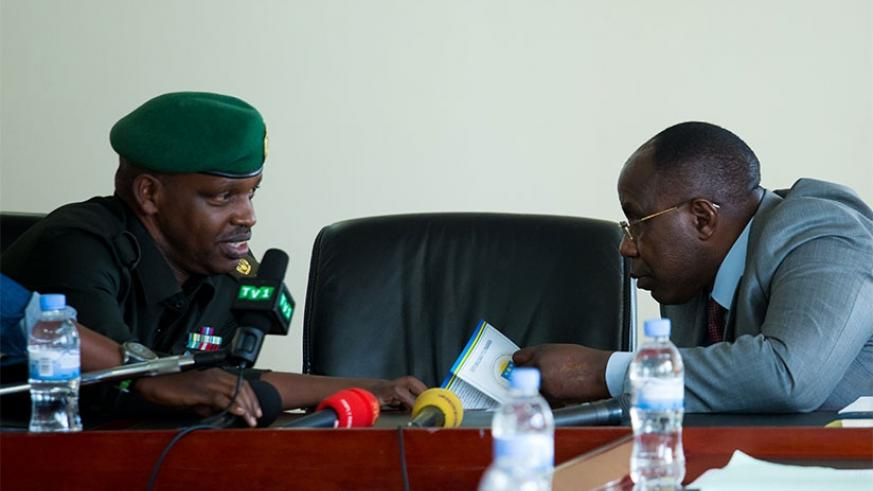 Lt col Nyirimanzi Gerard (L) speaks to Pierre-Damien Habumuremyi Chairman, Chancellery for Heroes, National Orders and Decorations of Honour before the press conference. (All photo....