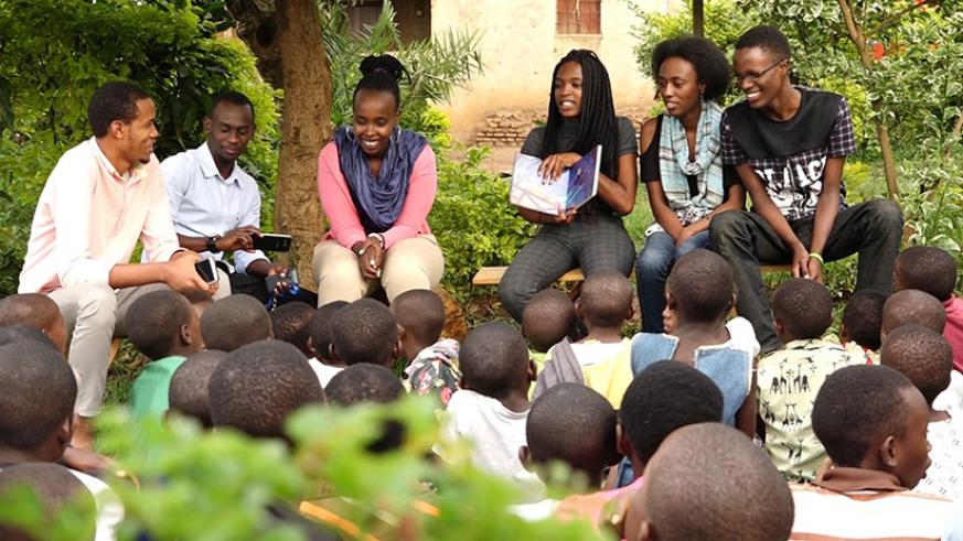 Dominique Uwase Alonga (centre right) reads a story to children at Ellie's Corner - a partner organization of Imagine We in Kigali. Courtesy.