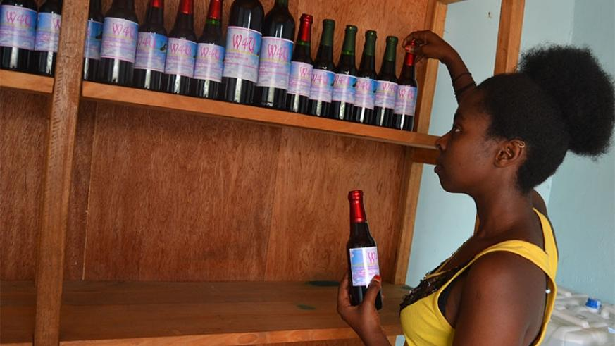 Uwamariya arranges bottles in her wine shop at Mahoko Centre in Rubavu District. Emmanuel Ntirenganya.