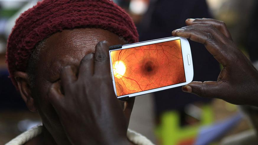 A woman undergoes an eye examination by use of a smartphone at a clinic in Kenya. / Net photo