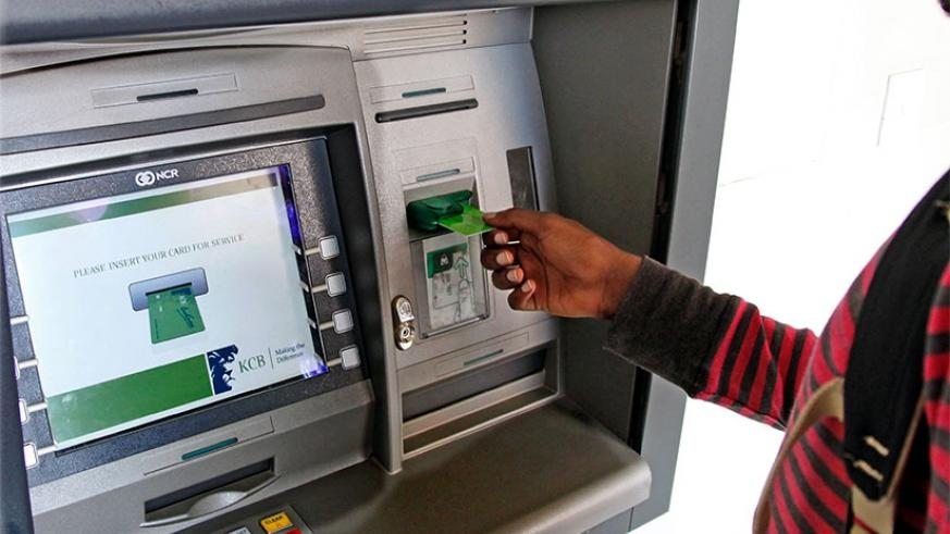 A bank client uses an automated card (Photo by T. Kisambira