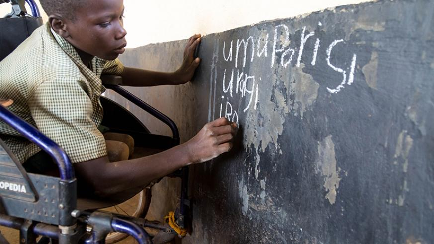 A child with disability writes on a blackboard at GS Bumbogo in Gasabo during a lesson. (Timothy Kisambira)