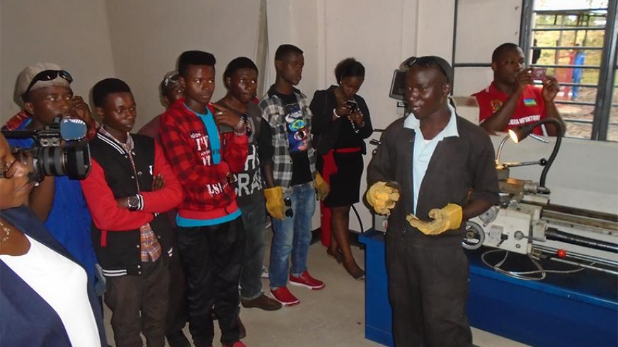 One of the students explains how the lathe machine works. (Photos by Steven Muvunyi)