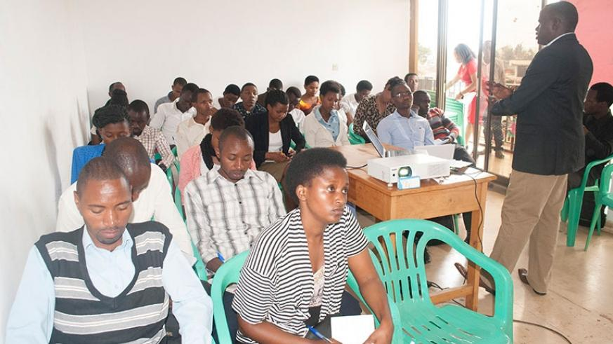 Faustin Mutabazi, the chief executive officer of Education Consultancy Bureau addresses the trainees. BELOW: Trainees follow proceedings during the one-day training in Remera, Kiga....