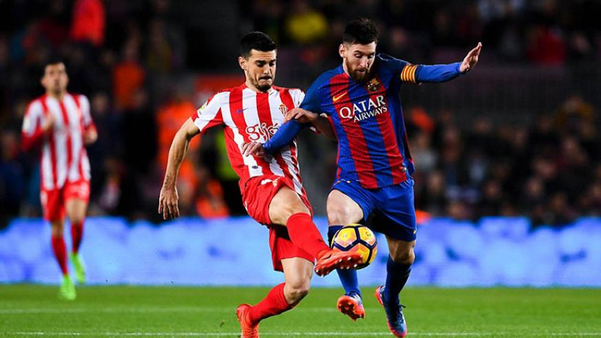Messi competes for the ball with Sergio Alvarez as Barcelona ended the game as a contest inside 10 minutes with two goals. / Getty Images