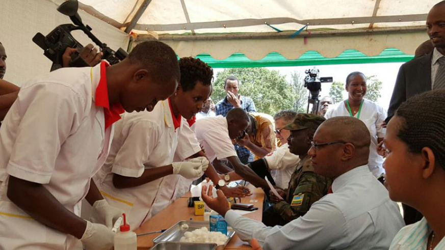 The State Minister for Public Health and Primary Healthcare, Dr Patrick Ndimubanzi (R), and other officials undergo health check-up from the newly-graduated healthcare practitioner....